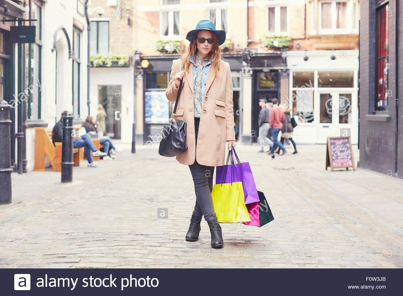 Portrait of stylish young woman on shopping spree, London, UK - Stock Image