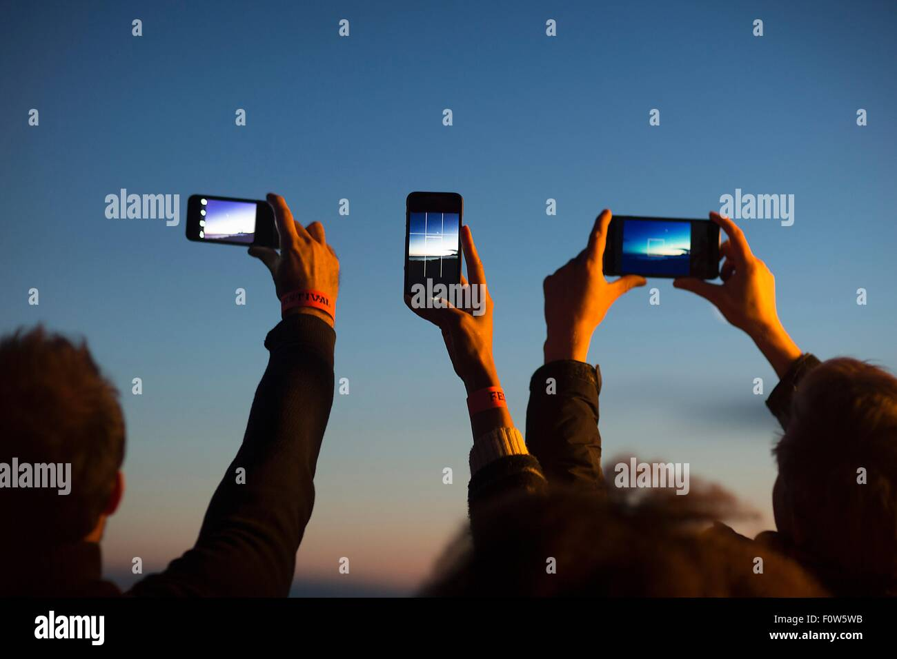 Friends taking photograph with smartphone at dusk - Stock Image
