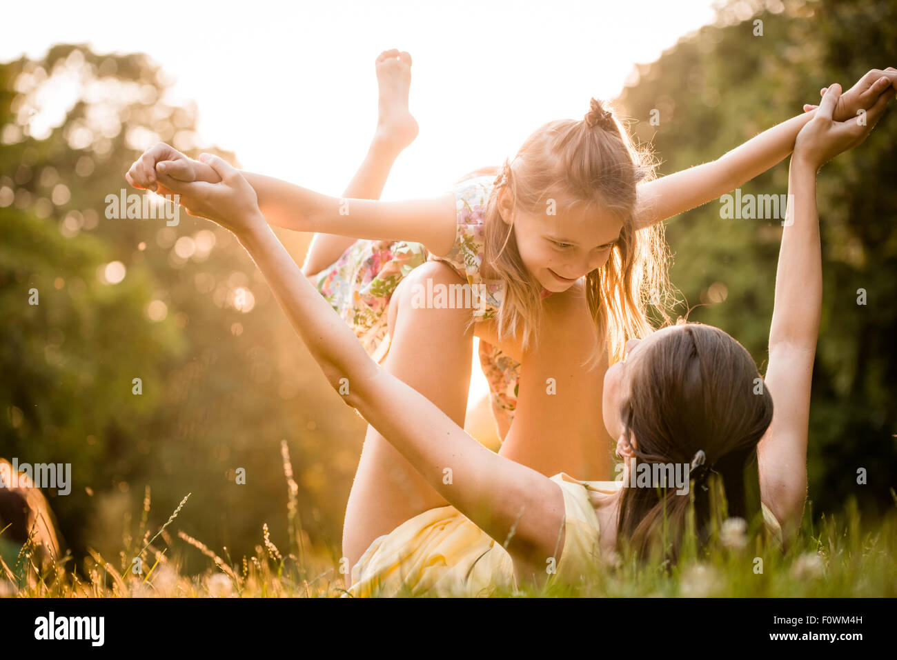 Mother lying down on grass and plays with her daughter on airplane - Stock Image
