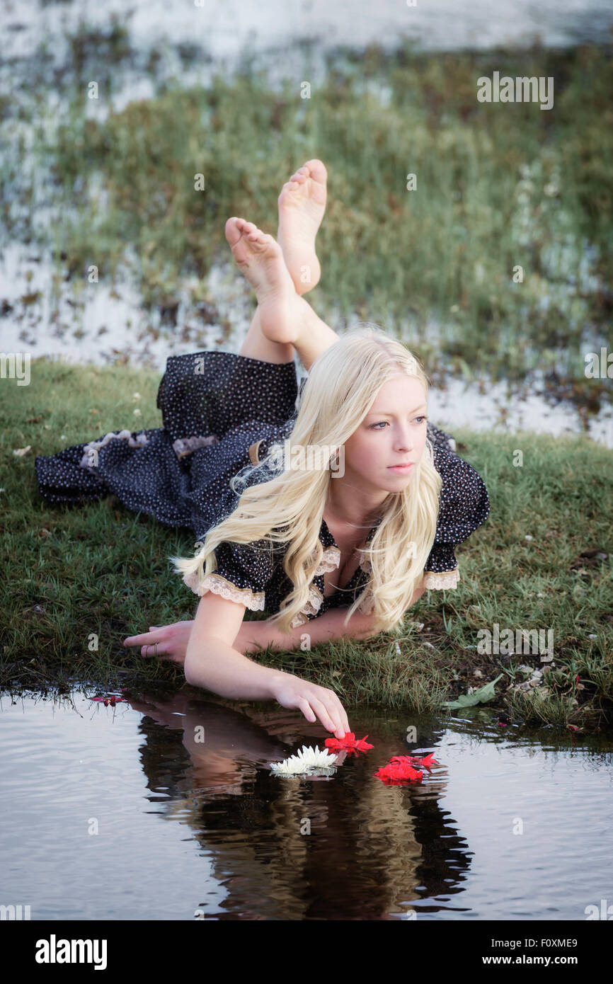 a blond girl is placing flowers on a pond - Stock Image