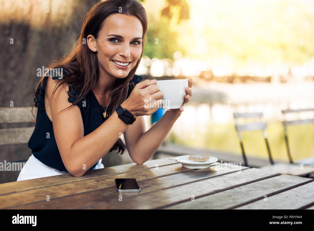 Portrait of beautiful young woman sitting at a table with a cup of coffee in hand looking at camera smiling while - Stock Image