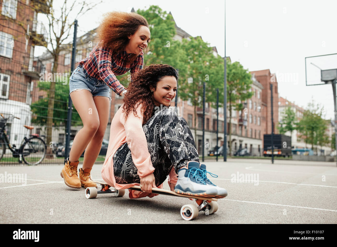 Happy young girl sitting on longboard being pushed by her friend. Young women enjoying skating outdoor. - Stock Image