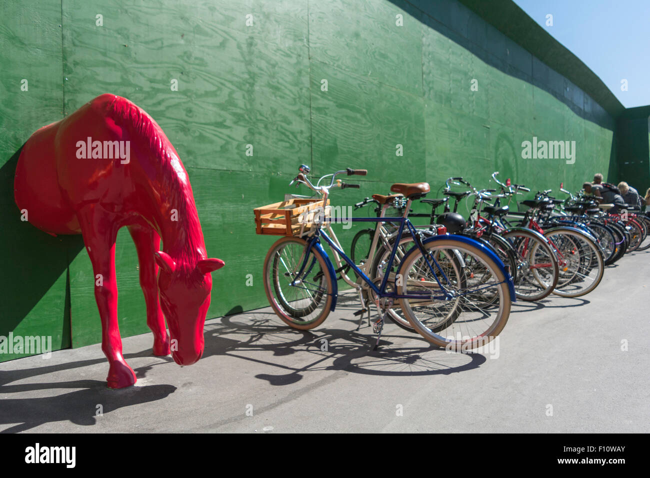 Half of a red horse juts out from green boarding adjacent to a rack of bicycles in Copenhagen, Denmark Stock Photo