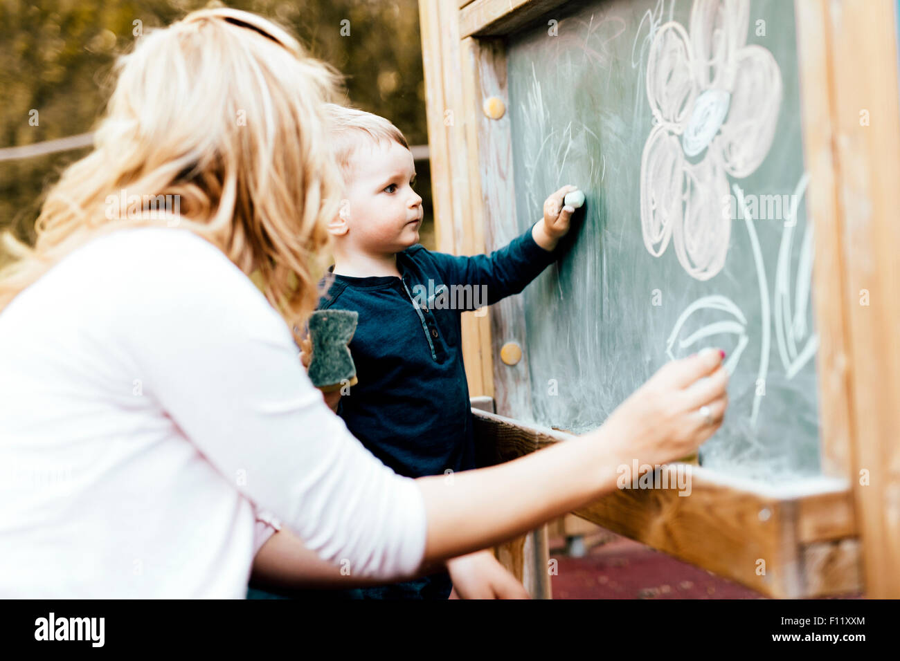 Beautiful mother and son drawing on blackboard with chalk - Stock Image