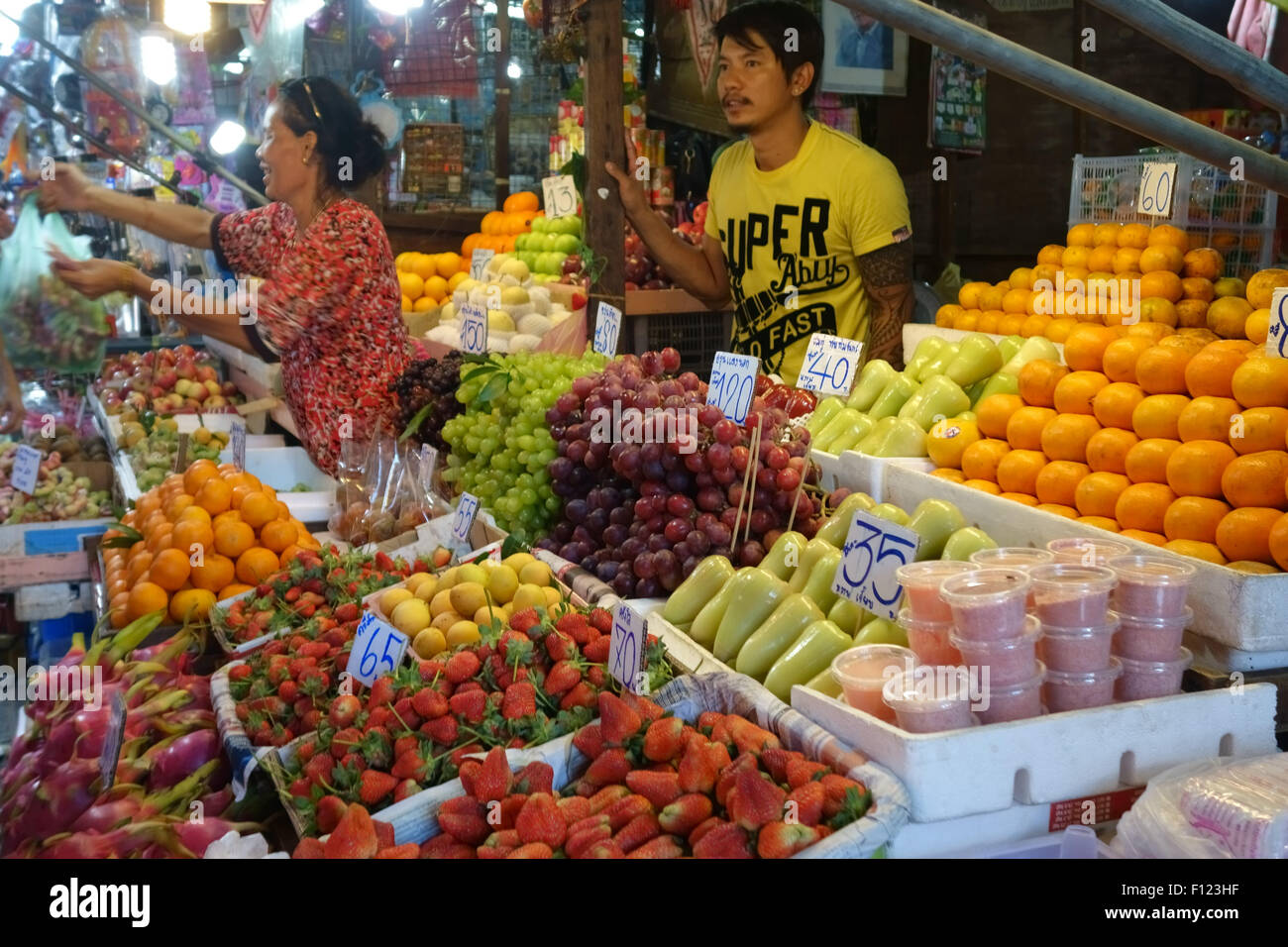 Fruit stall in a Bangkok food market with prices in Thai baht and a woman serving customers, Thailand - Stock Image