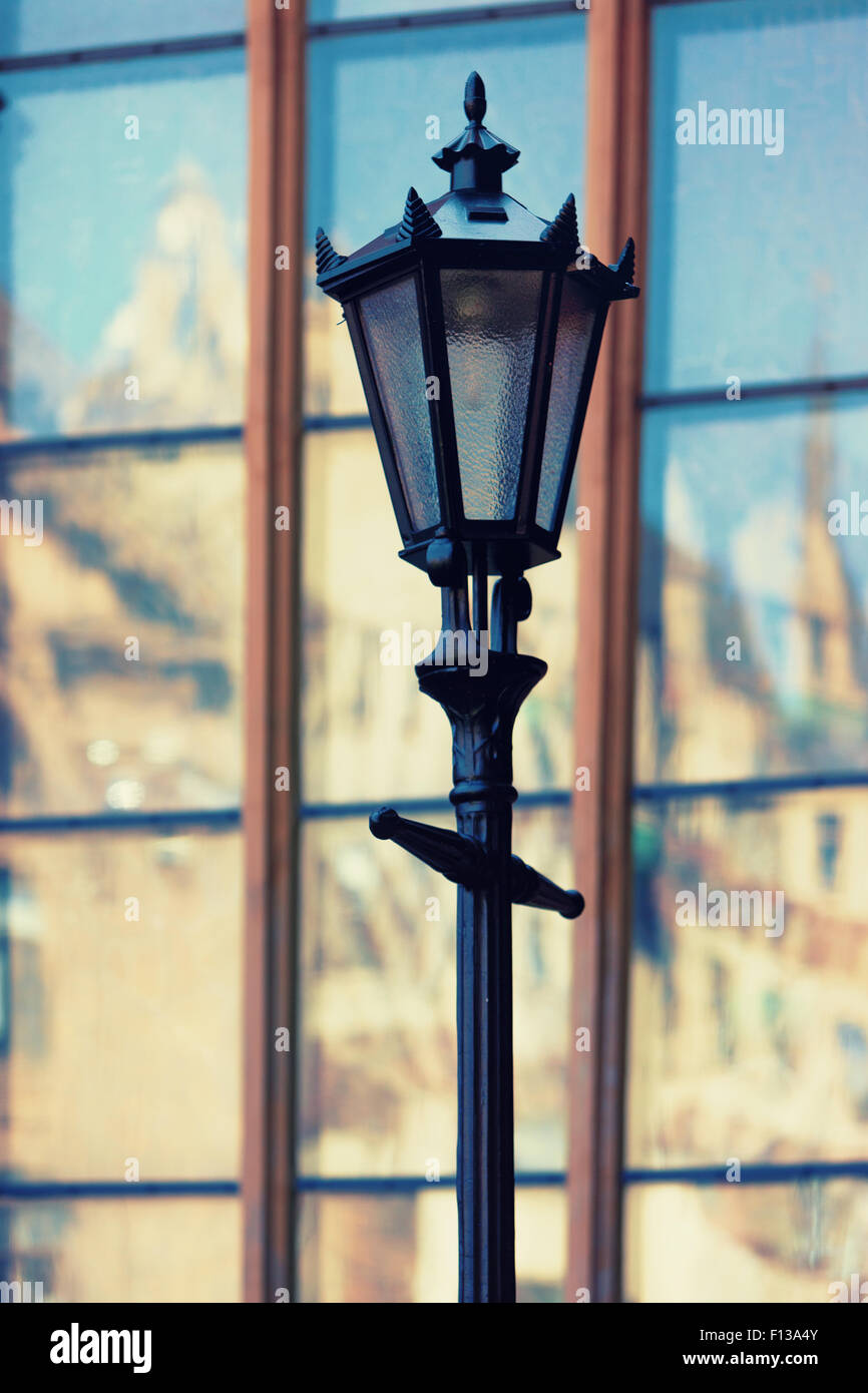 Latvia, Riga. Street lamp on the background of the reflection in the glass windows of old houses of the old town - Stock Image