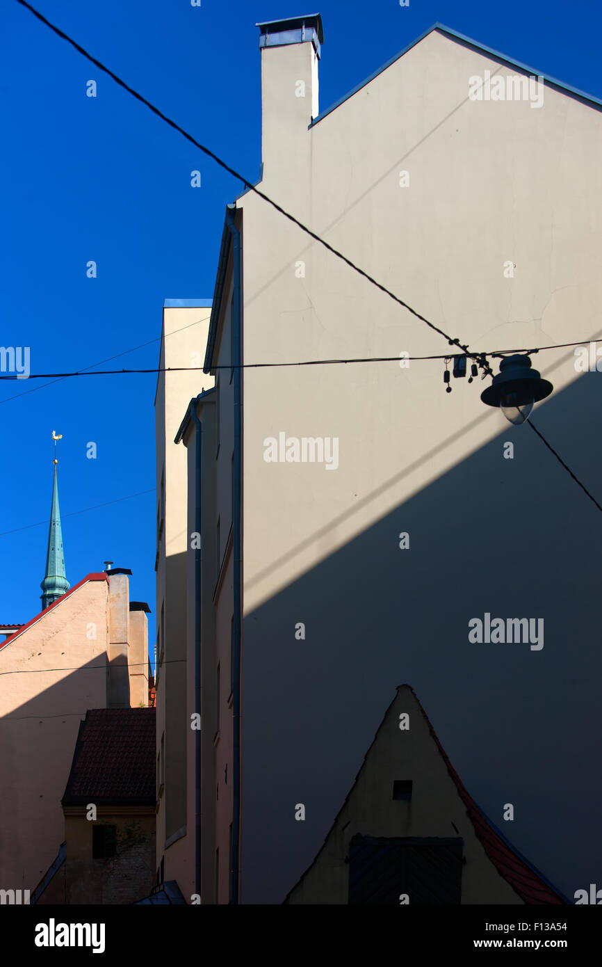Latvia. Riga. The unusual geometry of light and shadow facade and spire church cockerel against the blue sky of - Stock Image