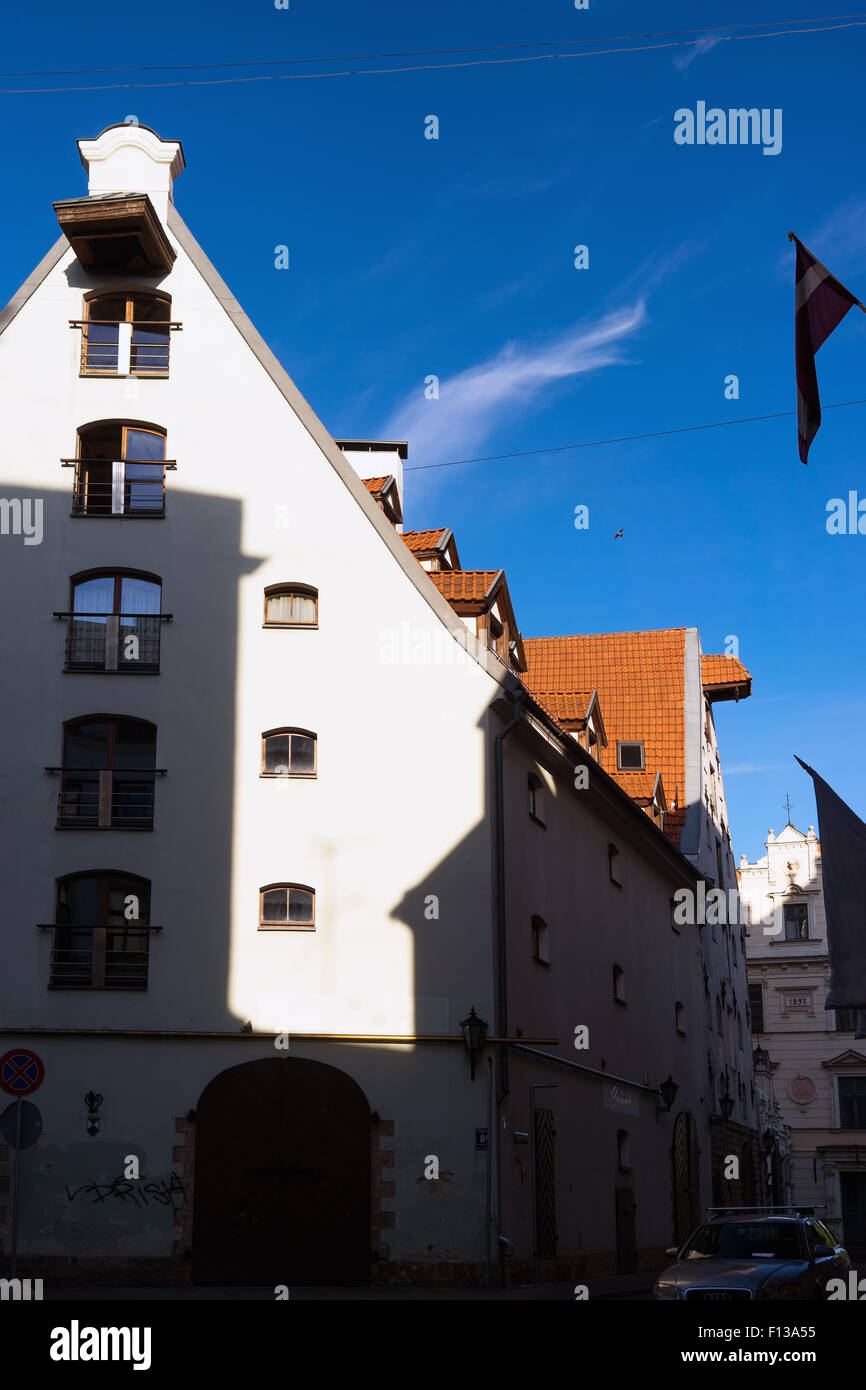 Latvia. The unusual geometry of light and shade facades and roofs against the blue sky of Riga on a summer day - Stock Image