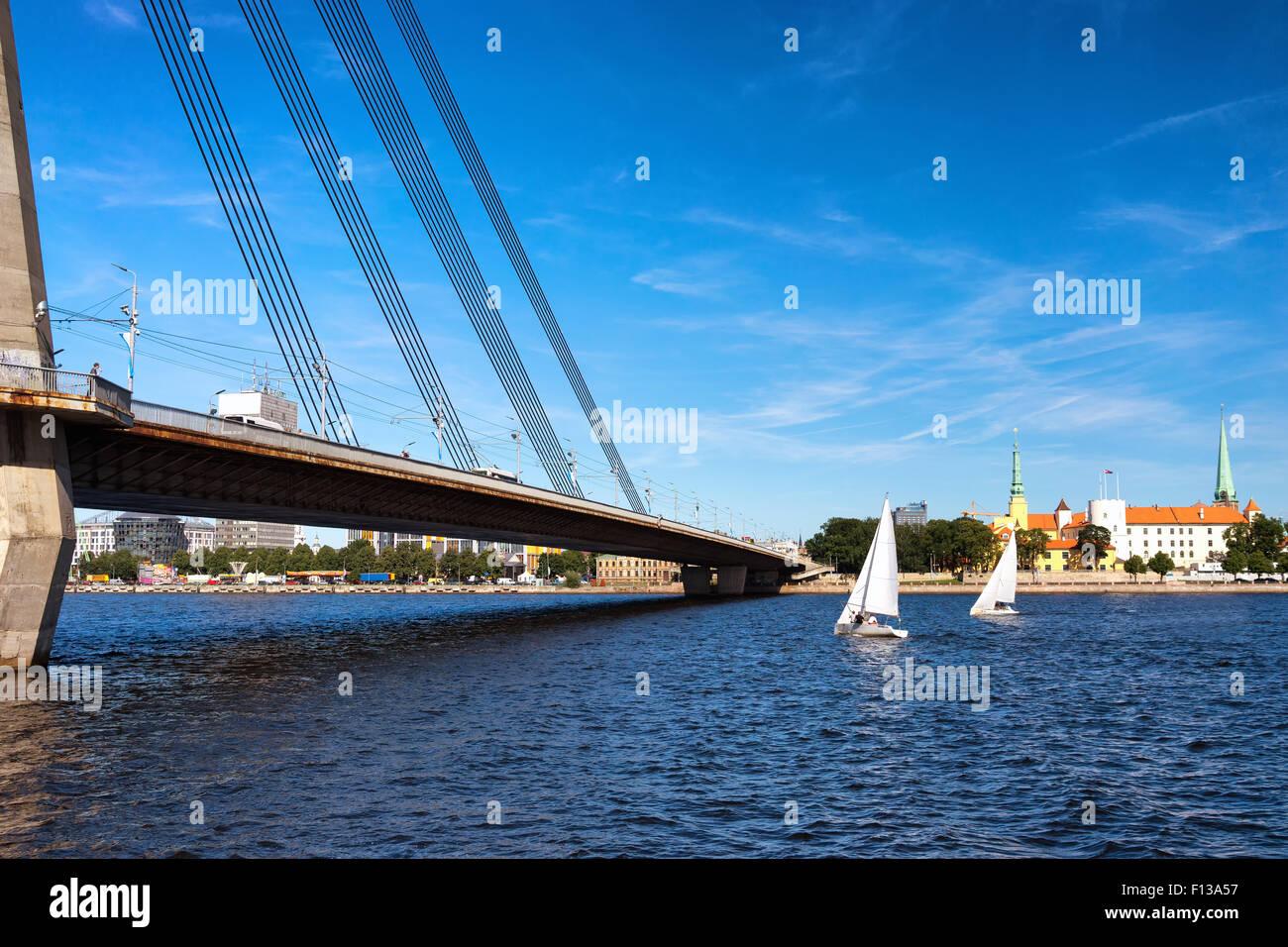 Latvia. Riga. Sailboat on the Daugava River near the cable-stayed bridge and the palace of the President of Latvia - Stock Image