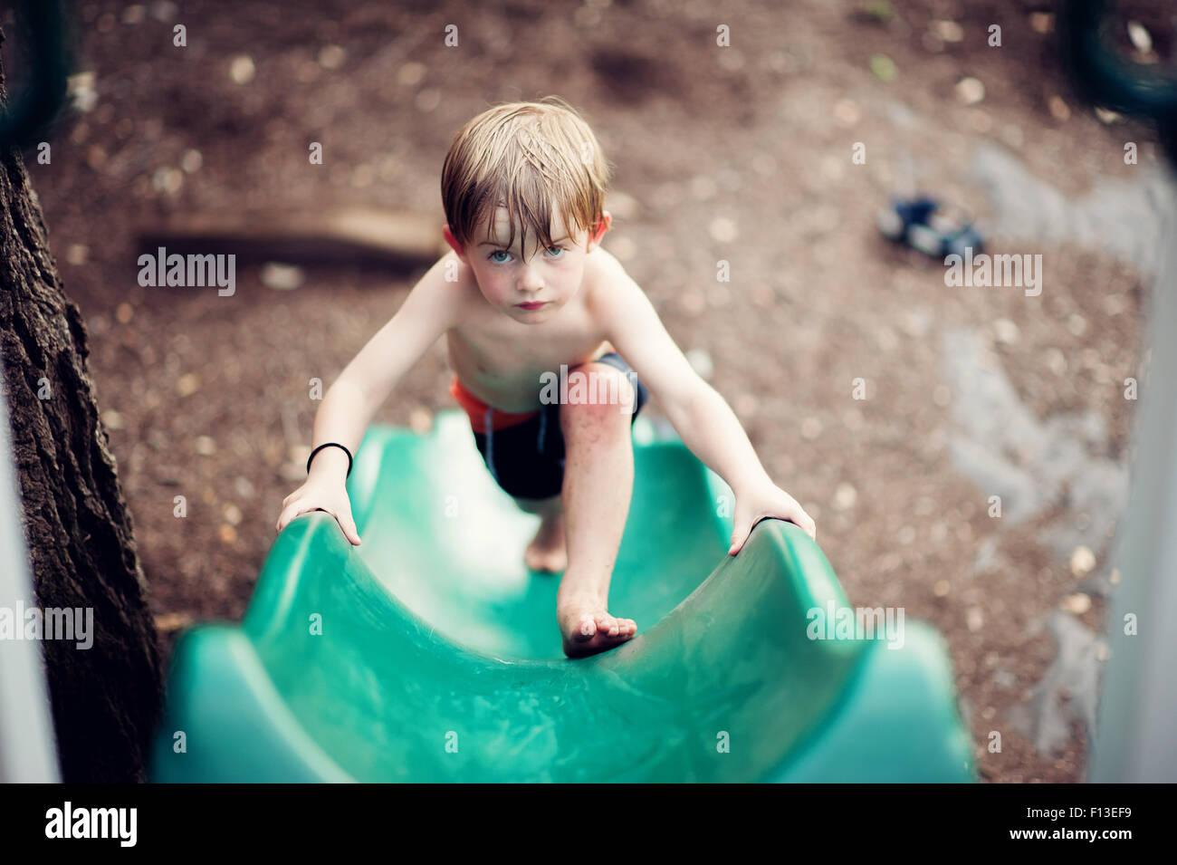 Boy climbing up a slide - Stock Image