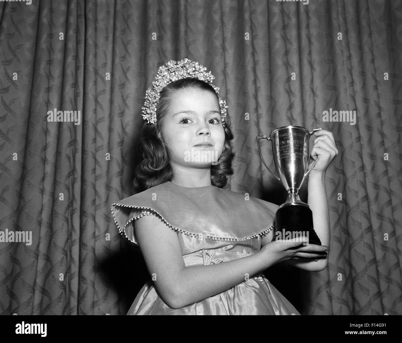 1950s 1960s YOUNG GIRL STANDING WITH TROPHY LOVING CUP WEARING TIARA PRETTY DRESS WINNER OF BEAUTY PAGEANT LOOKING Stock Photo