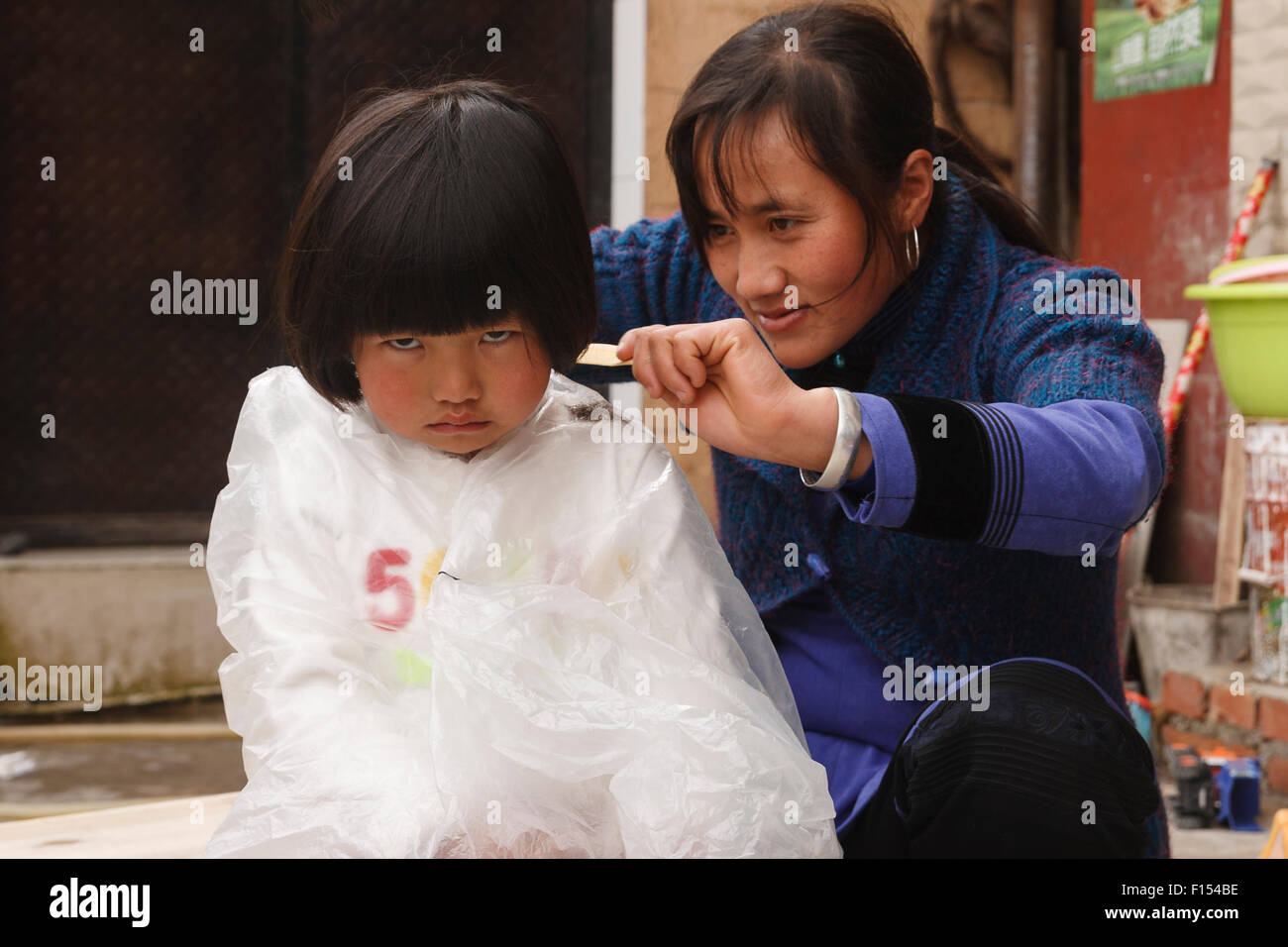 5 Year Old Hani Chinese Girl Sulking Having Her Hair Cut In Street
