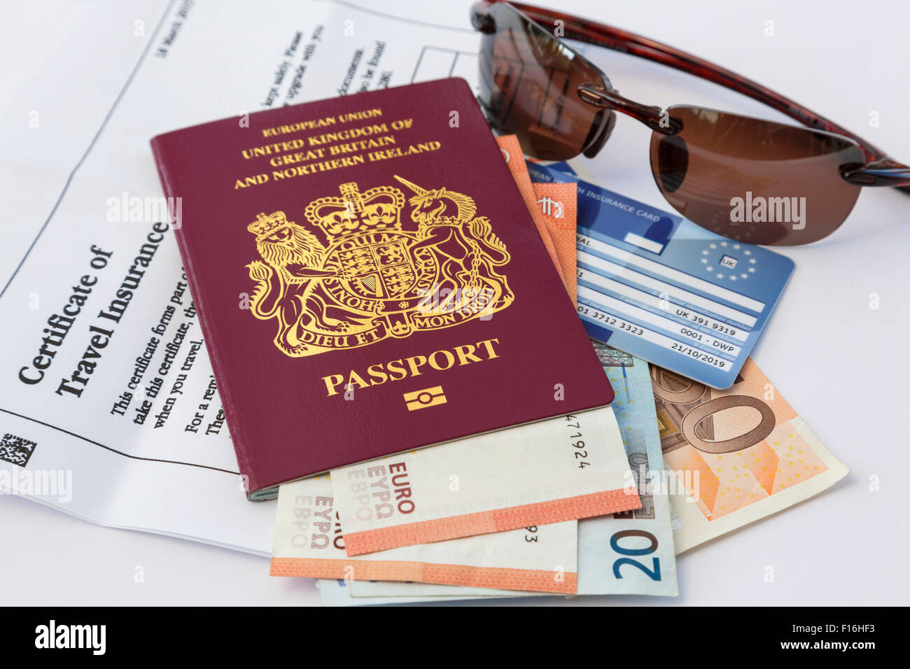British passport travel insurance documents and currency money EHIC card and sunglasses for travelling to Eurozone Stock Photo