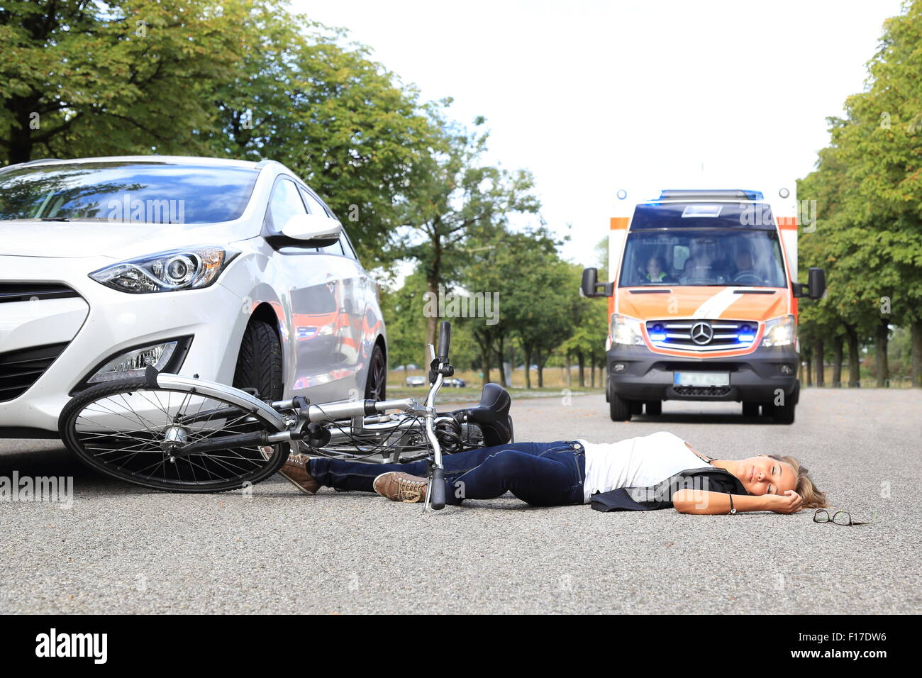A Young Woman with bicycle accident and comming ambulance car - Stock Image
