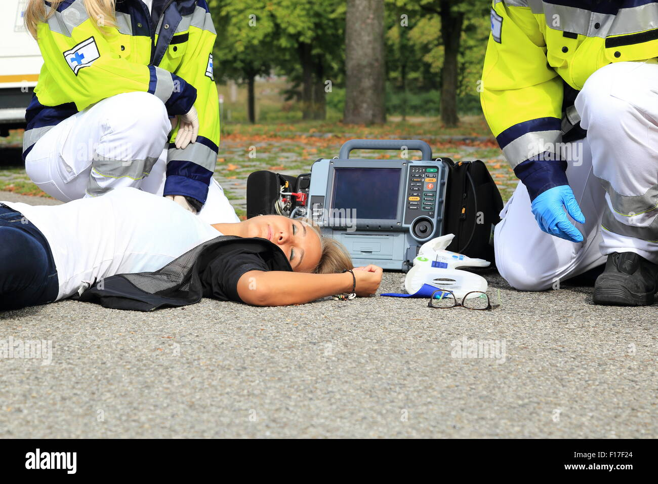 A Woman after Accident with paramedic and defibrillator first aid - Stock Image