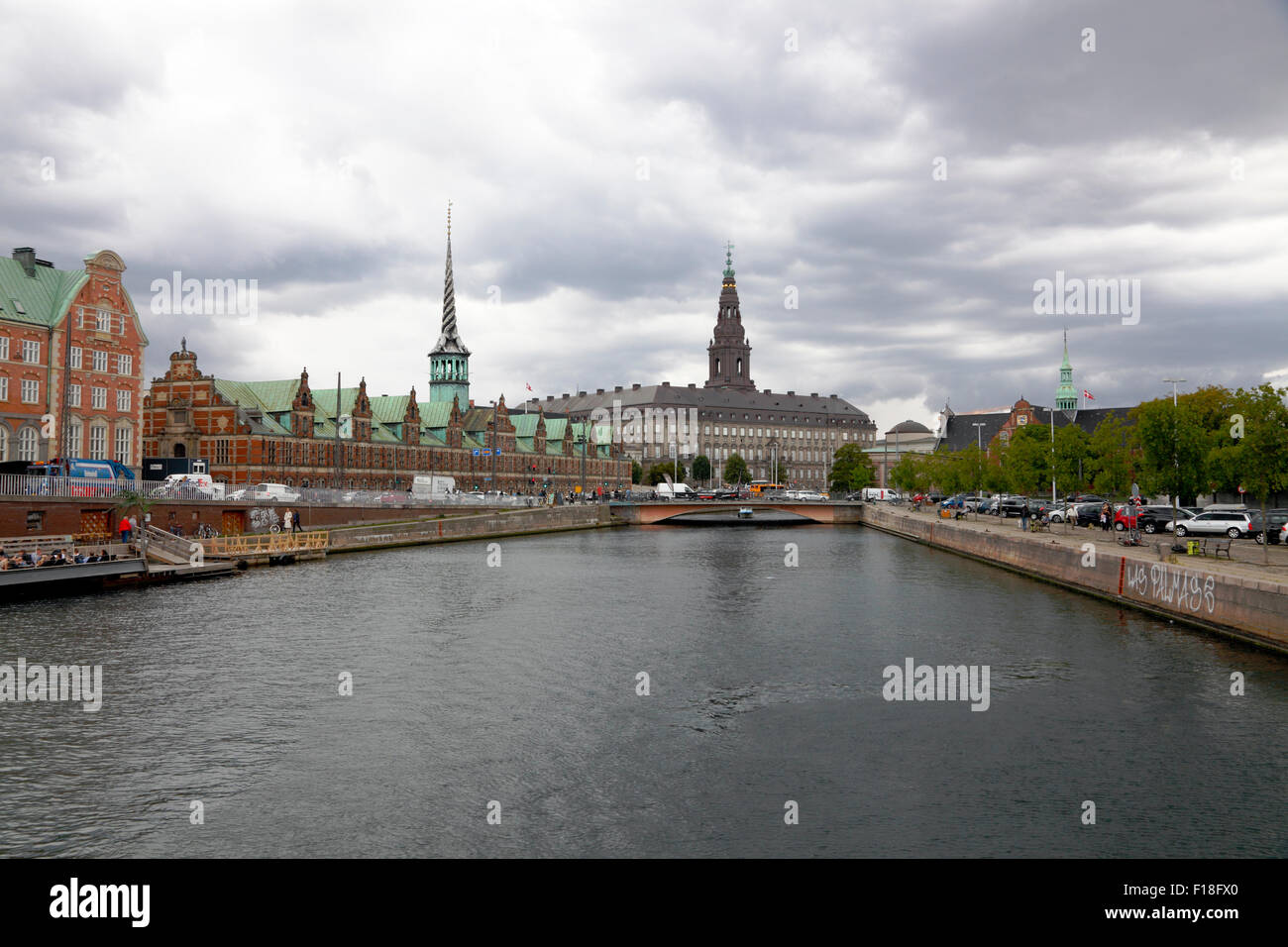 View of the Old Stock Exchange and Christiansborg Castle  from Christian the 4ths Bridge on a summer day with threatening - Stock Image