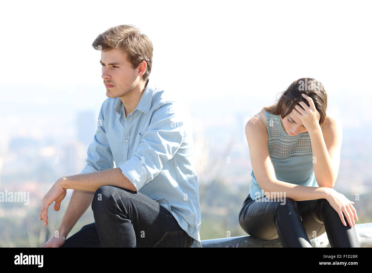 Bad boy arguing with his couple breakup concept with the city in the background - Stock Image