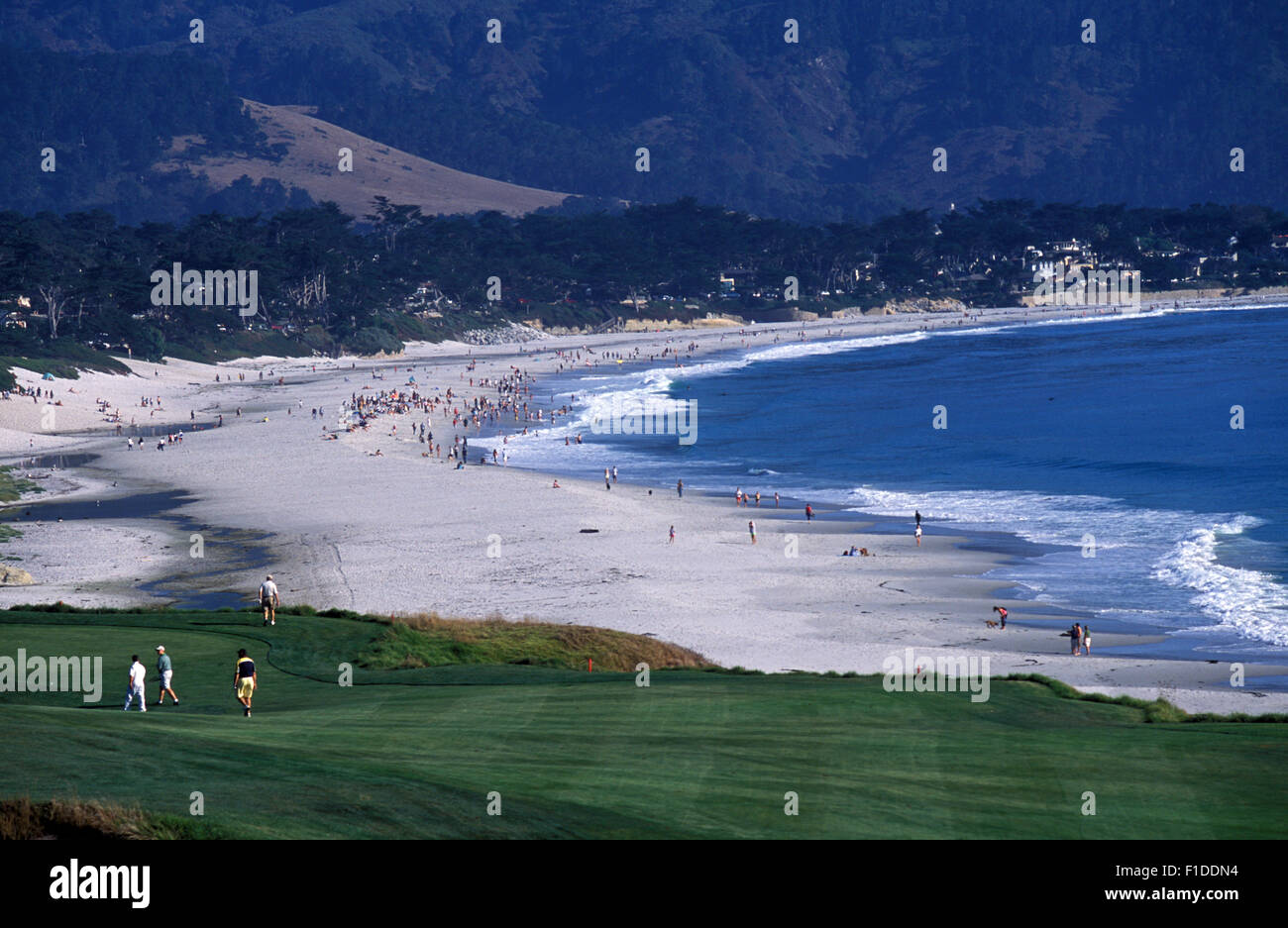People playing golf in Pebble Beach Golf with the Carmel Beach in Carmel-by-the-Sea, or simply Carmel. Stock Photo