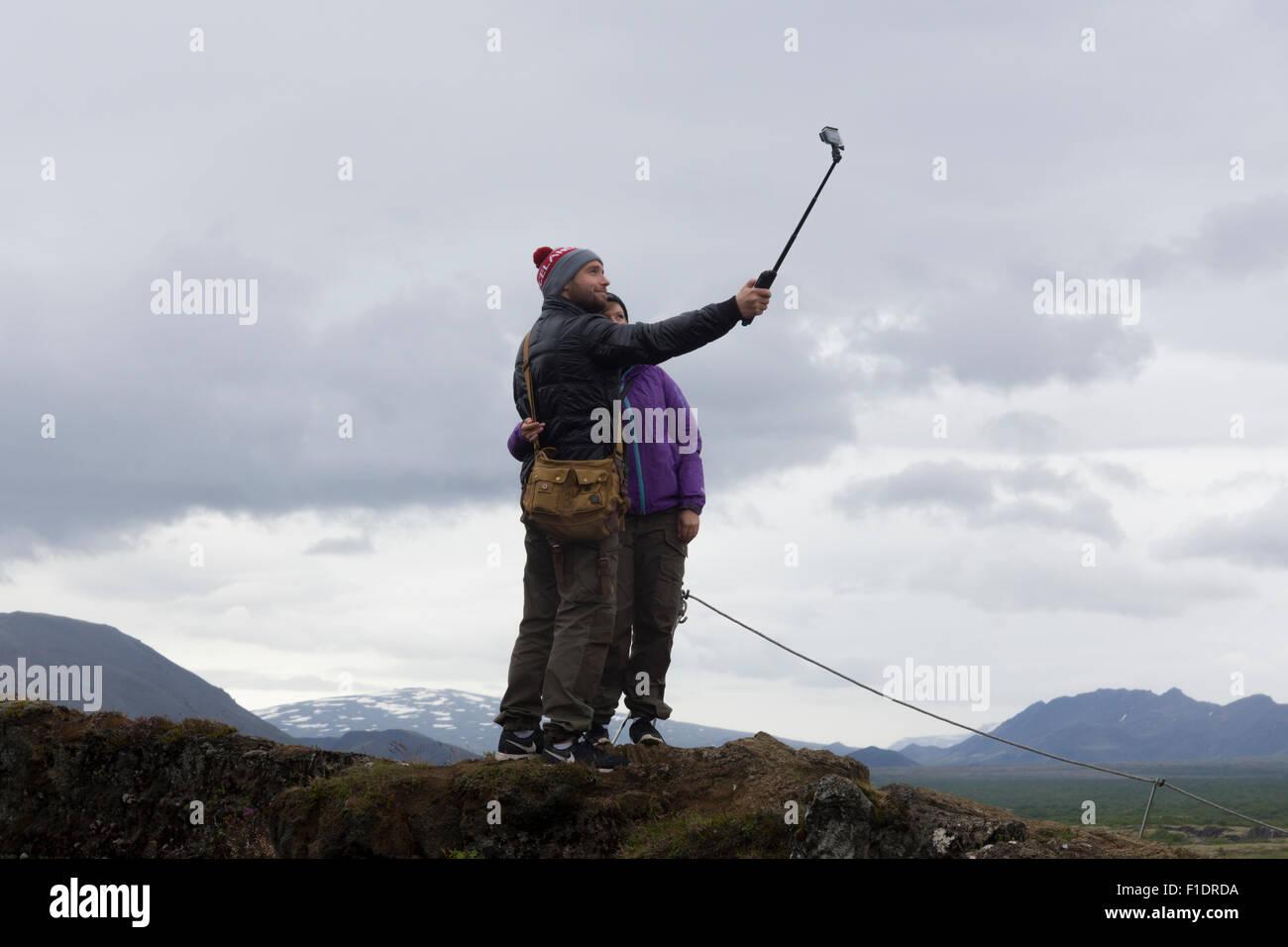 a-couple-using-a-selfie-stick-in-pingvellir-national-park-iceland-F1DRDA.jpg