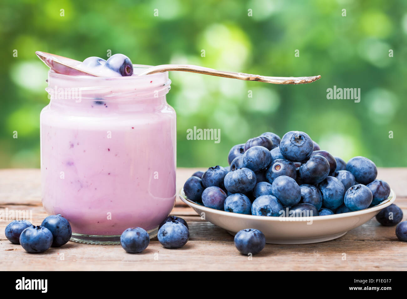 Fresh blueberries yogurt in glass jar and saucer with bilberries. - Stock Image