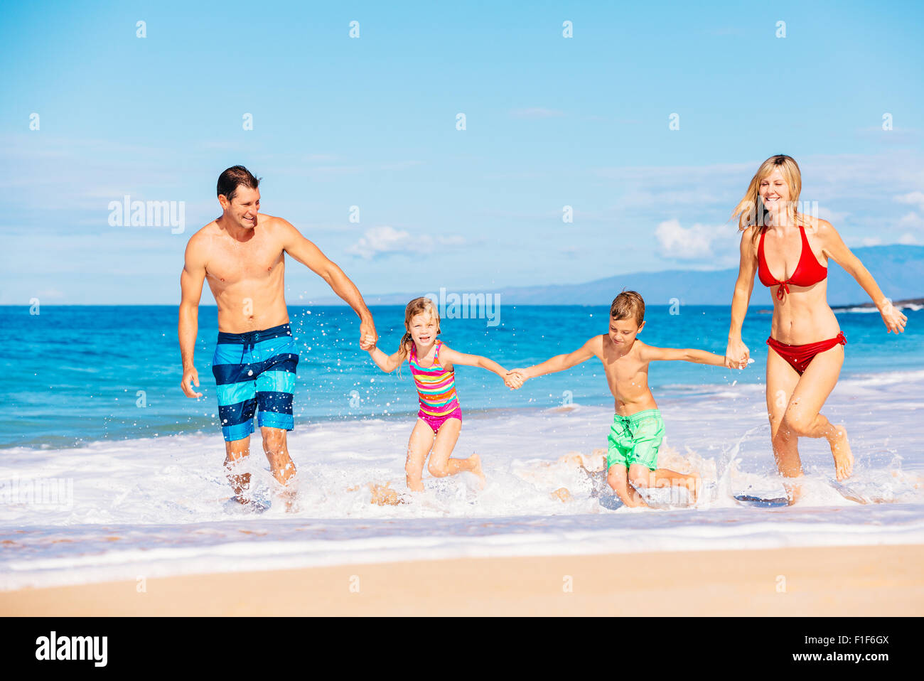 Family vacation. Happy family having fun on beautiful warm sunny beach. Outdoor summer lifestyle. - Stock Image