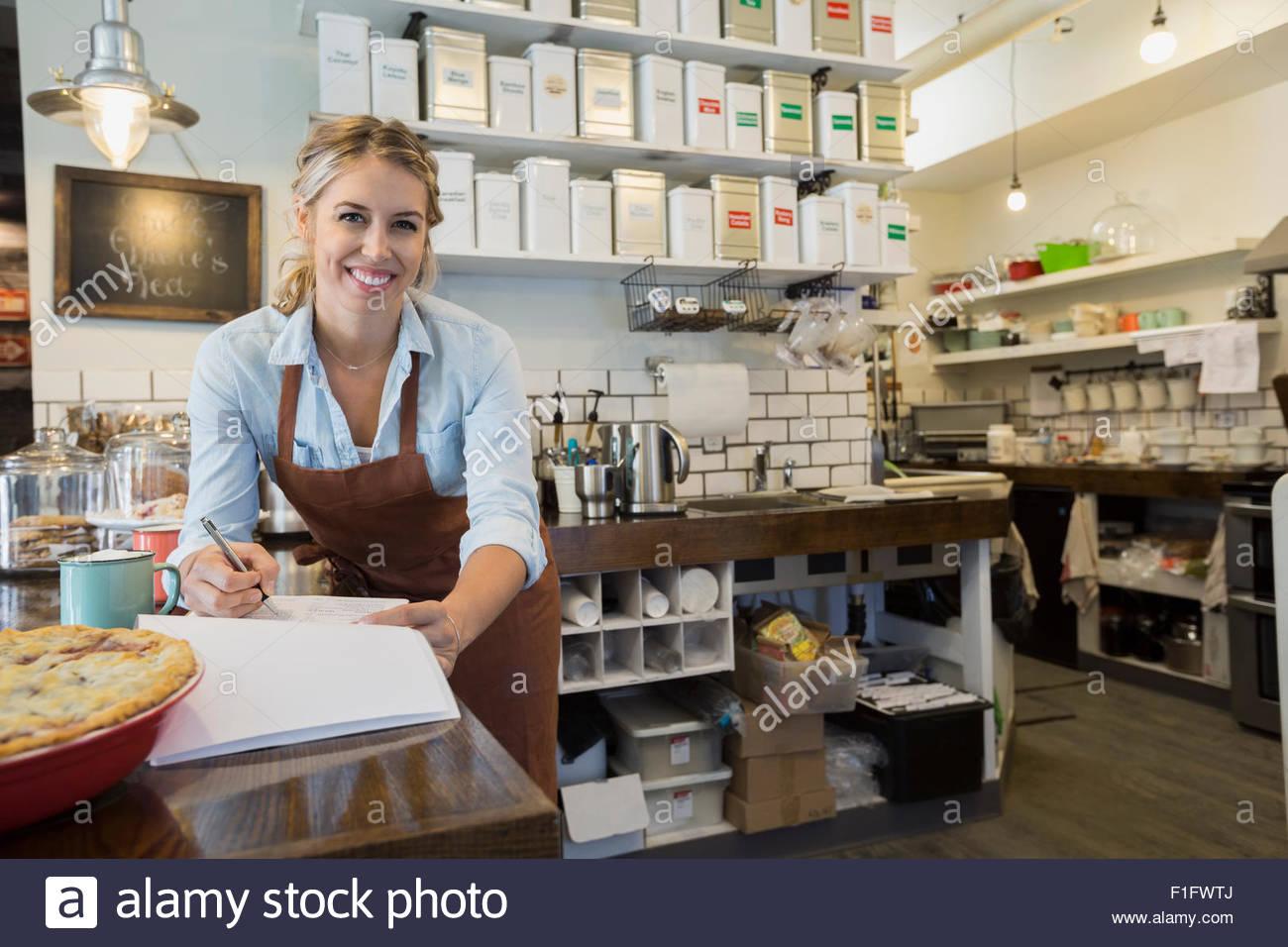 Portrait confident tea shop owner doing paperwork counter - Stock Image