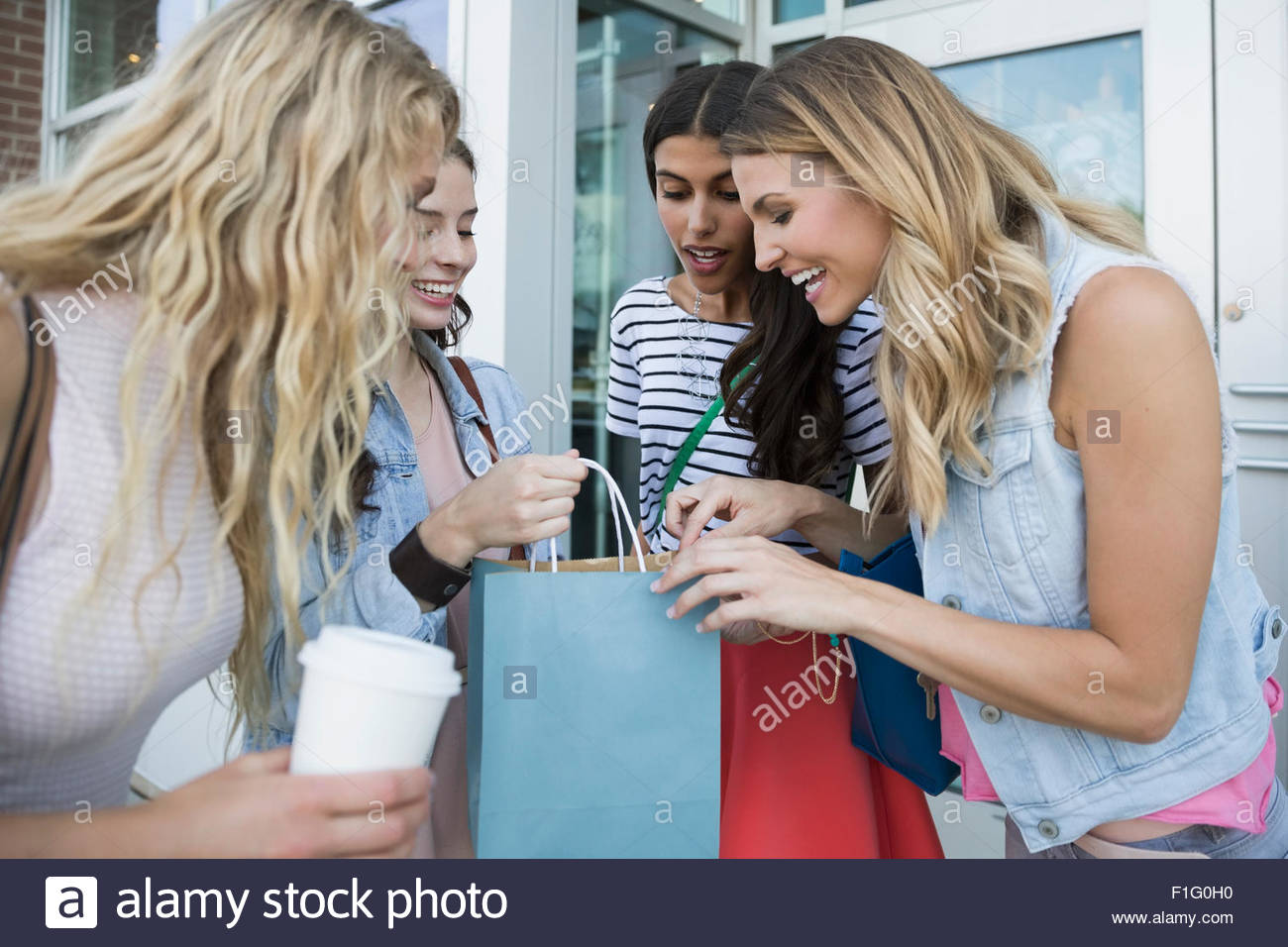 Women looking inside shopping bags at storefront - Stock Image