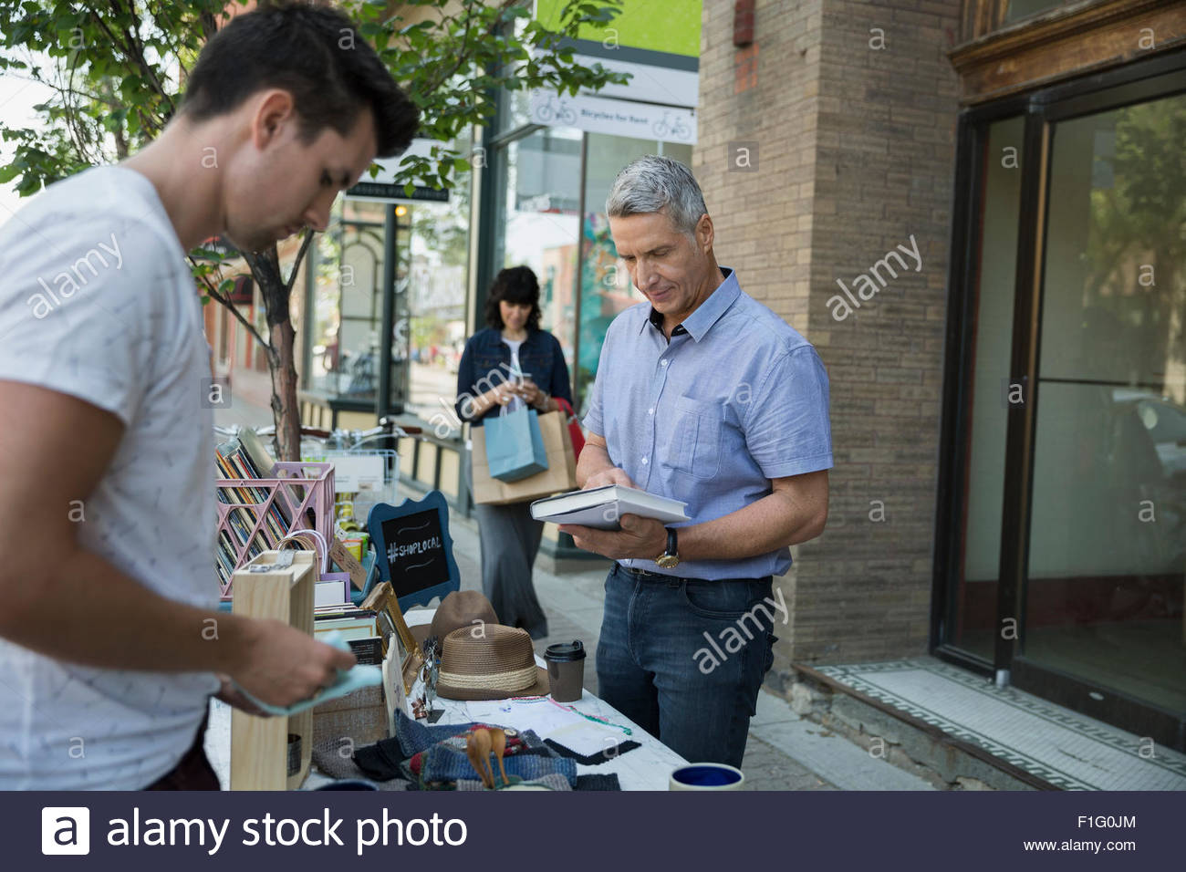 Man browsing book at sidewalk sale - Stock Image