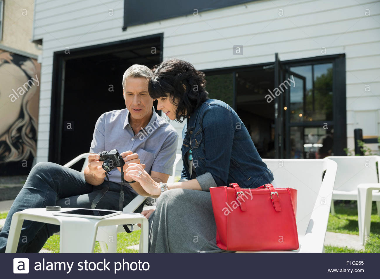 Couple looking at digital camera on sunny patio - Stock Image