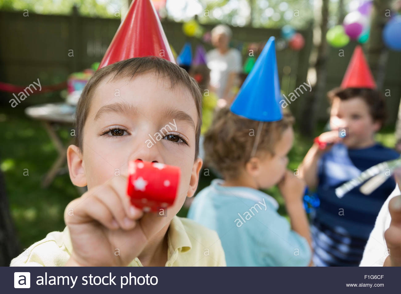 Portrait boy blowing birthday party favor - Stock Image