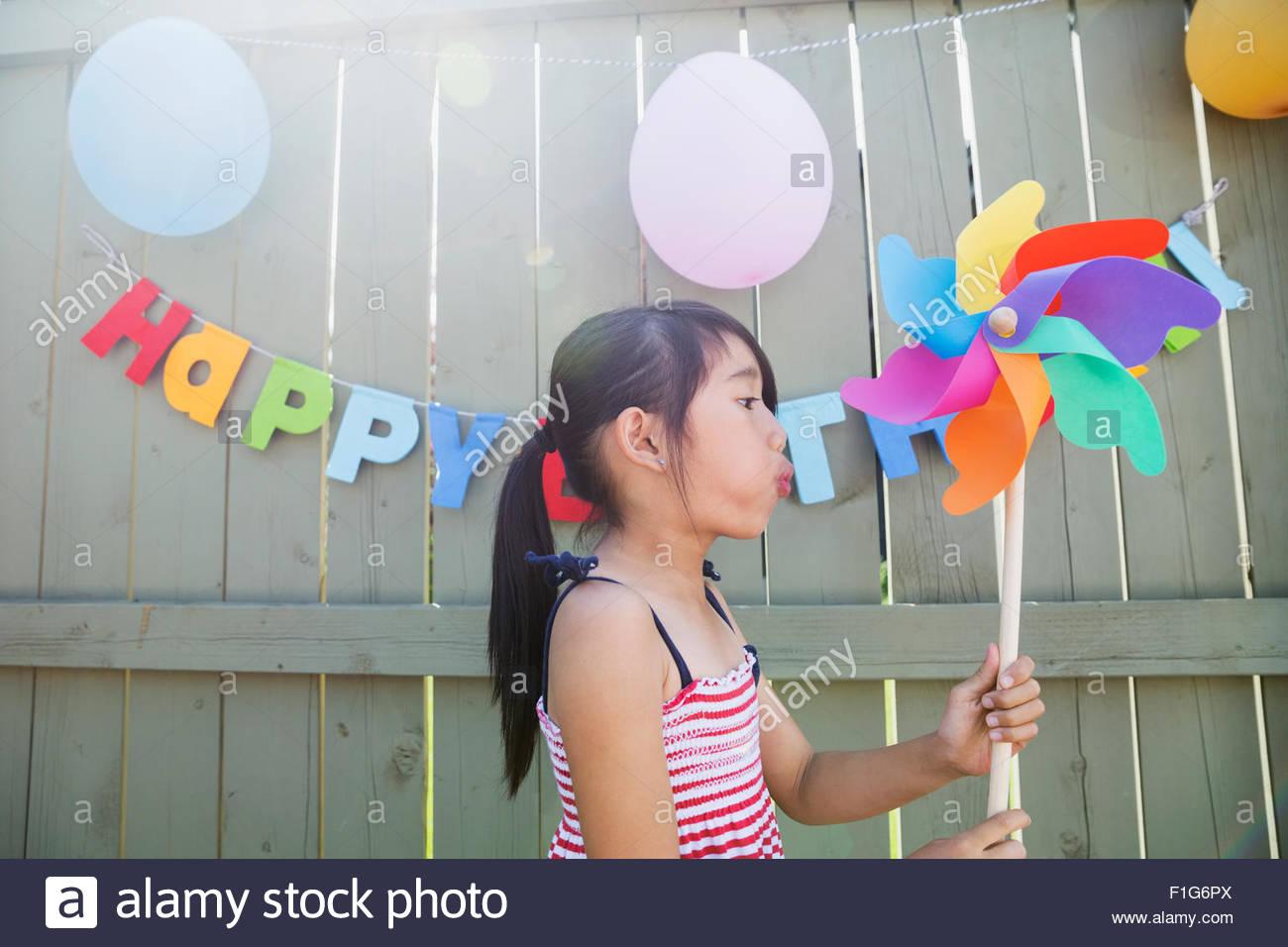 Girl blowing pinwheel at backyard birthday party - Stock Image