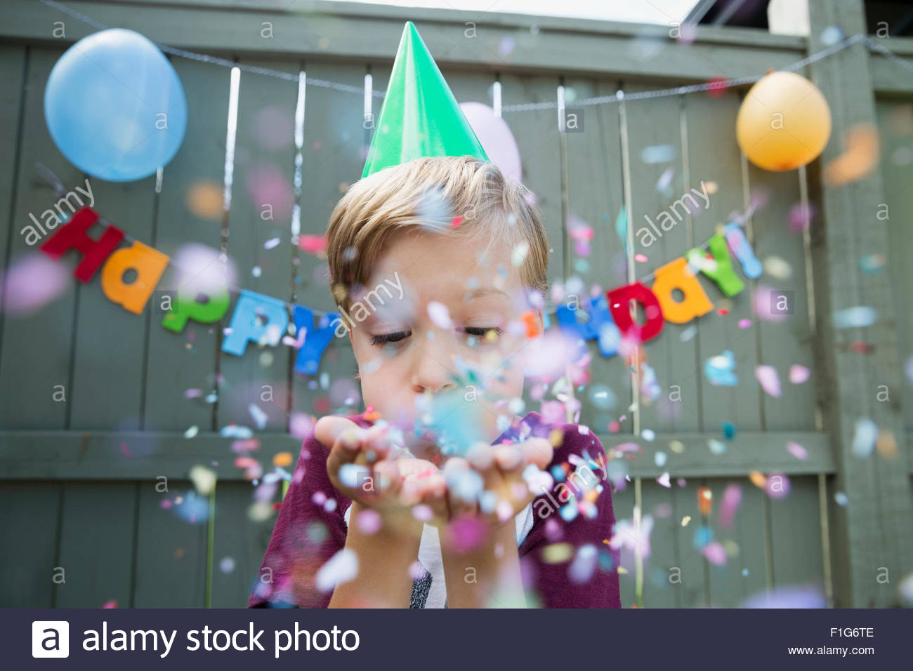 Boy blowing confetti wearing birthday party hat - Stock Image