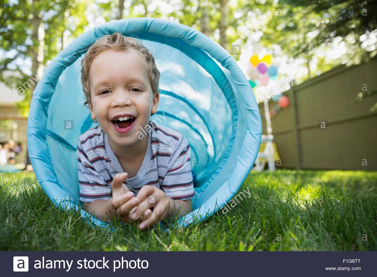 Portrait smiling boy inside toy tunnel in backyard - Stock Image