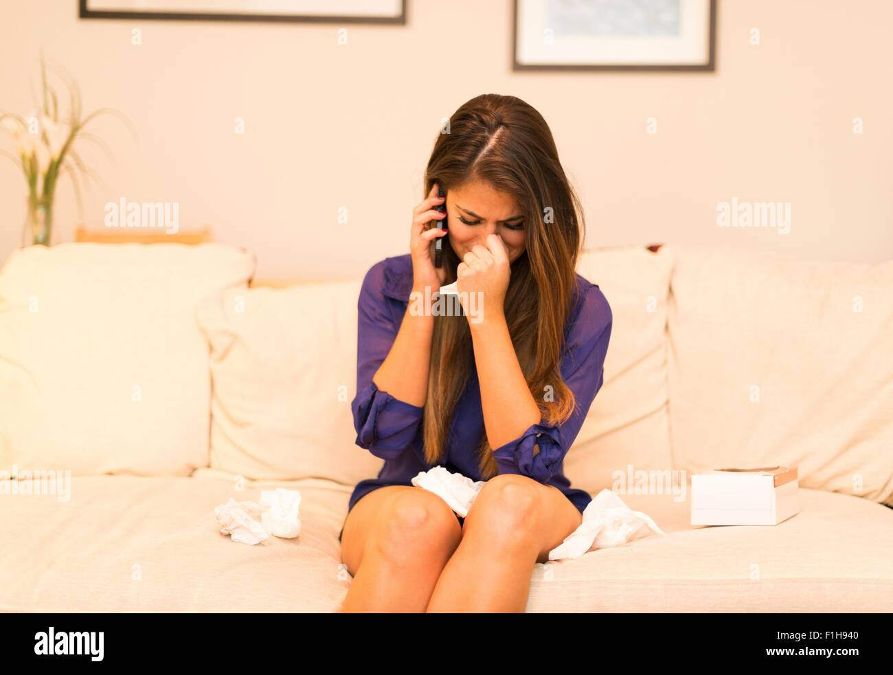 Young woman having telephone conversation, crying - Stock Image