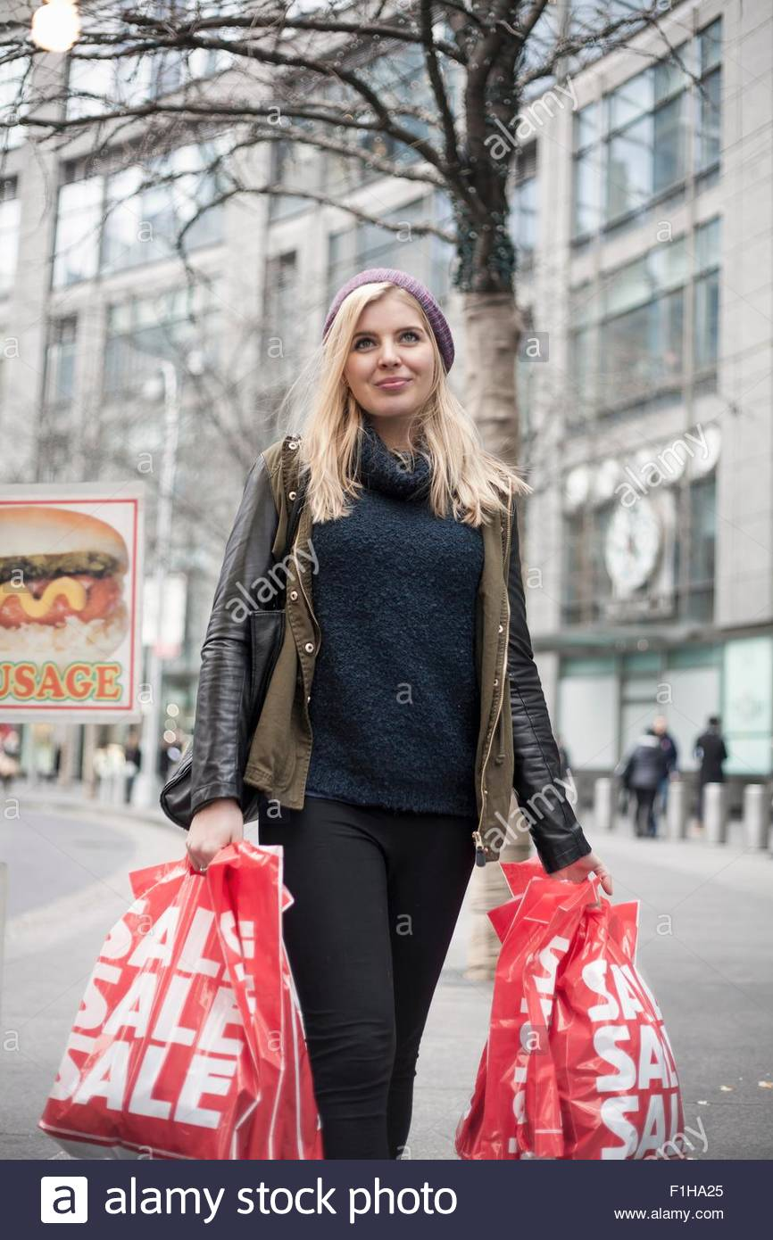 Young woman carrying sale shopping bags on street,  New York, USA - Stock Image