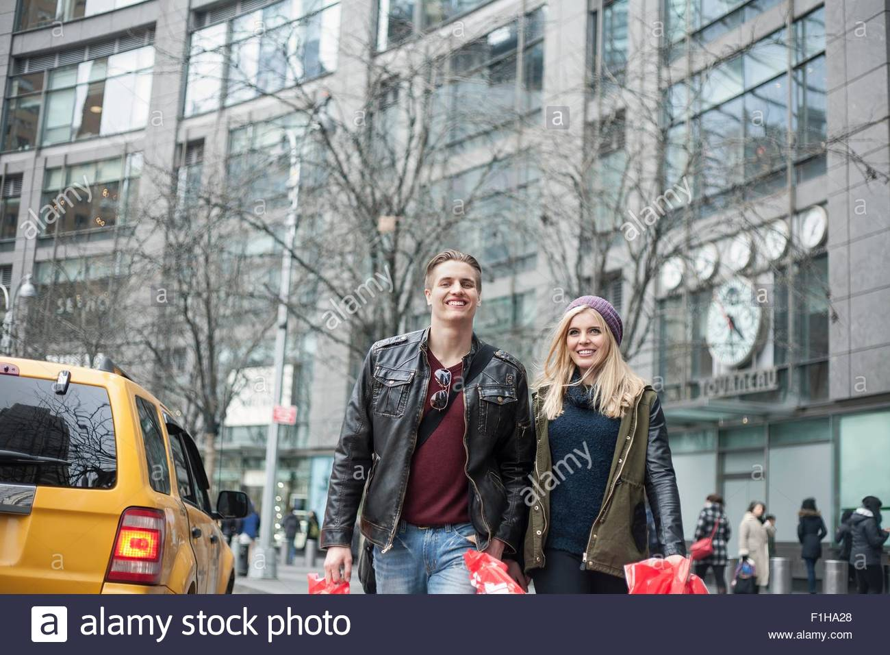 Young couple strolling with shopping bags on street,  New York, USA - Stock Image