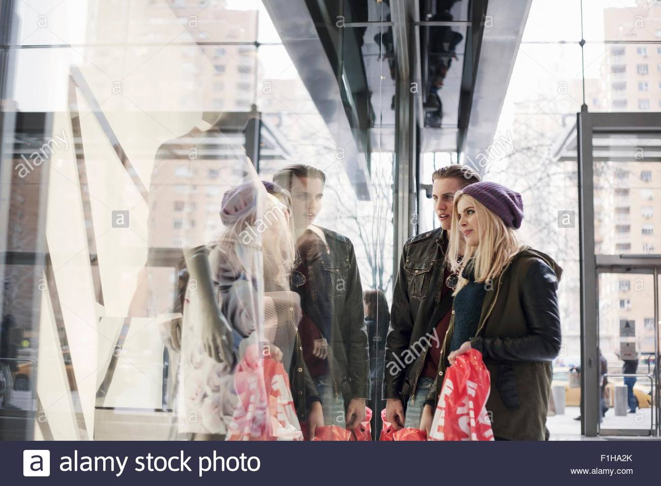 Young couple gazing at shop window with sale shopping bags,  New York, USA - Stock Image