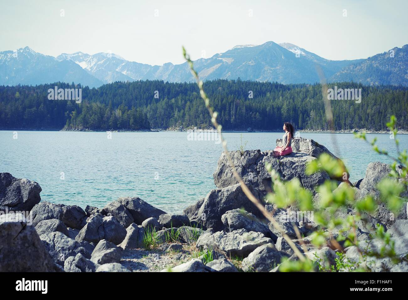 Mid adult woman, sitting on rock, in yoga position - Stock Image