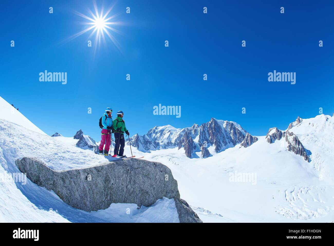Male and female skiers looking out from ridge on Mont Blanc massif, Graian Alps, France - Stock Image