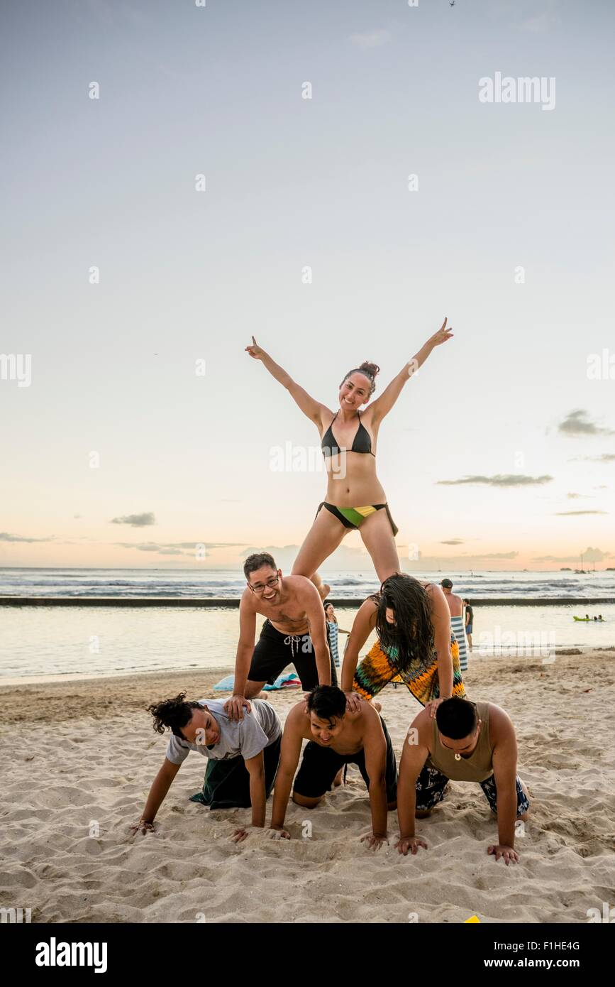 Six adult friends forming human pyramid on Waikiki Beach, Hawaii