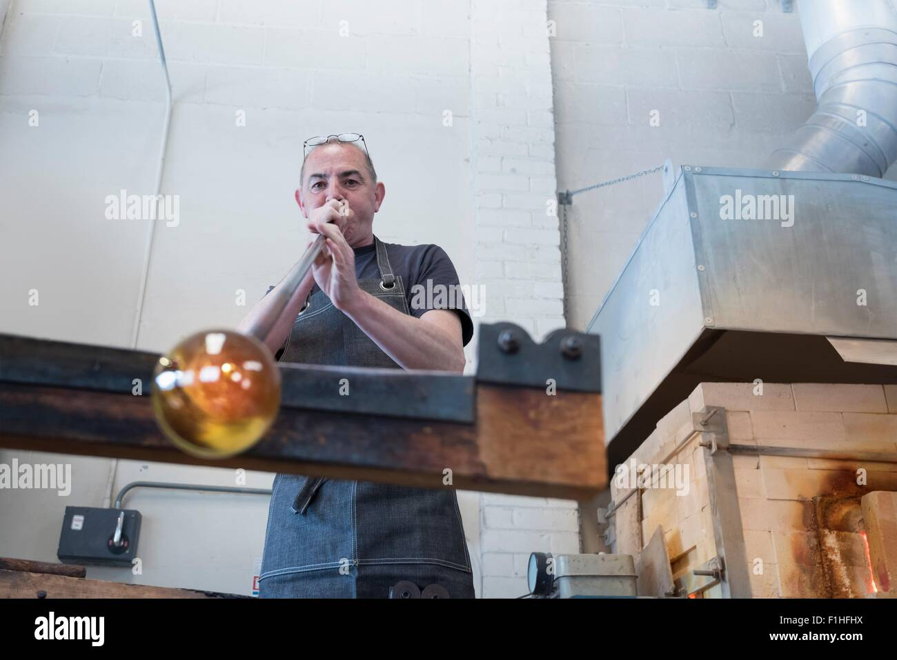 Glassblower blowing hot glass - Stock Image