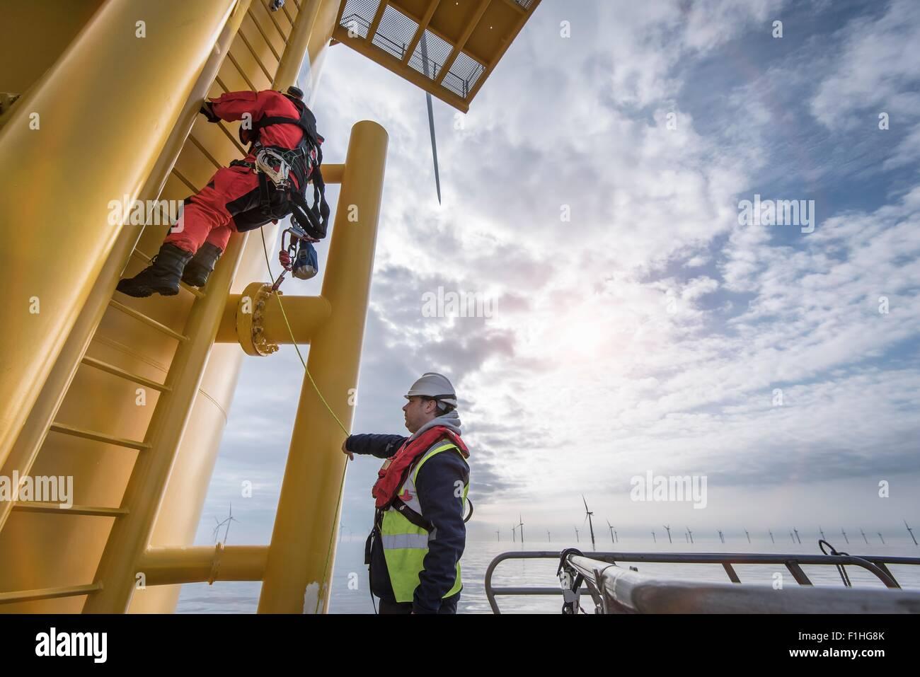 Engineer climbing wind turbine at offshore windfarm - Stock Image