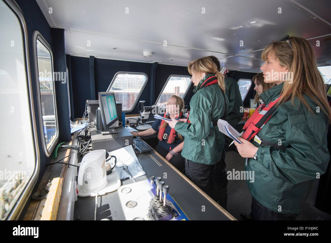 Marine biologists in laboratory on research ship - Stock Image
