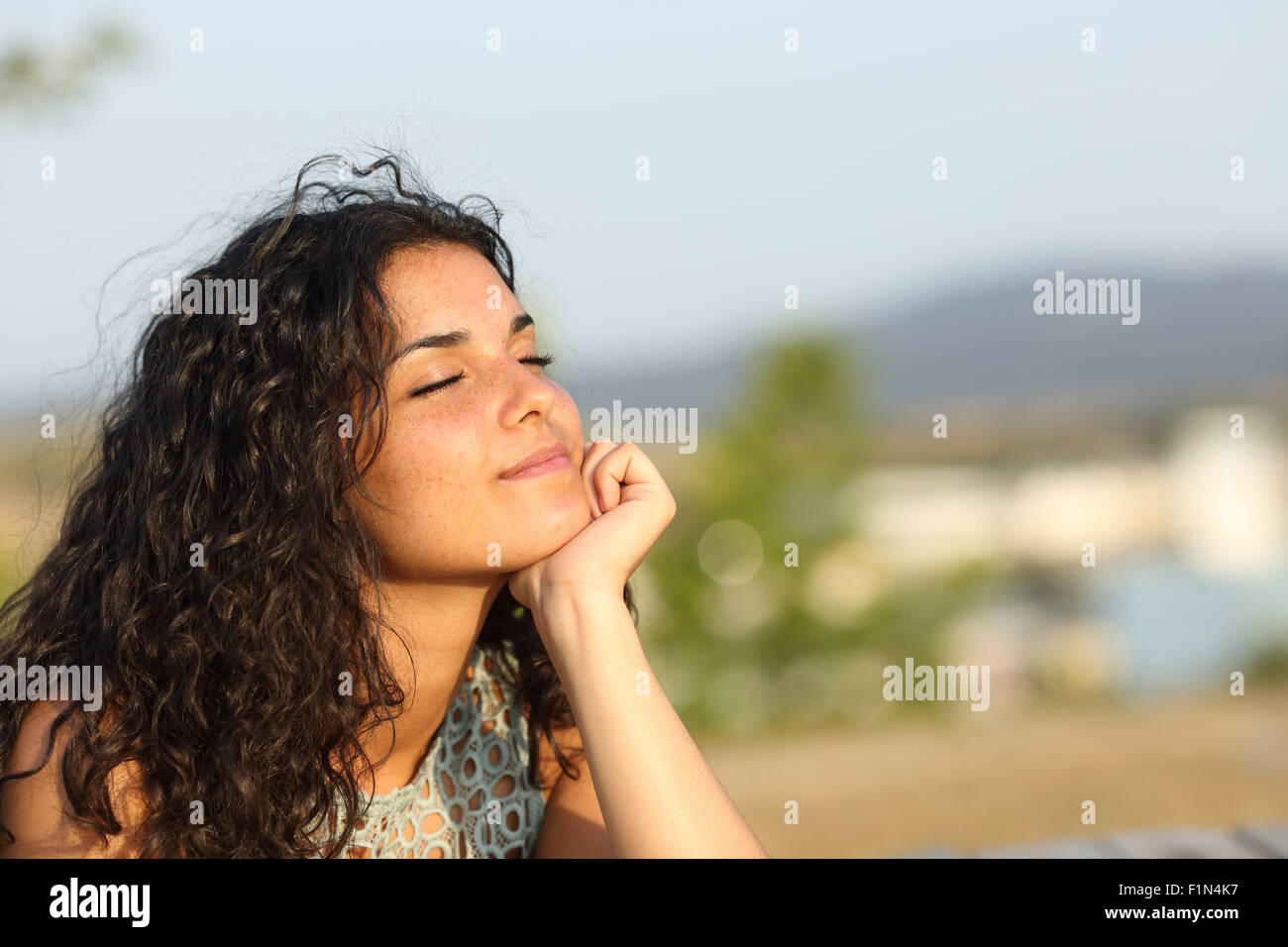 Woman relaxing and enjoying the sun in a warmth park at sunset - Stock Image