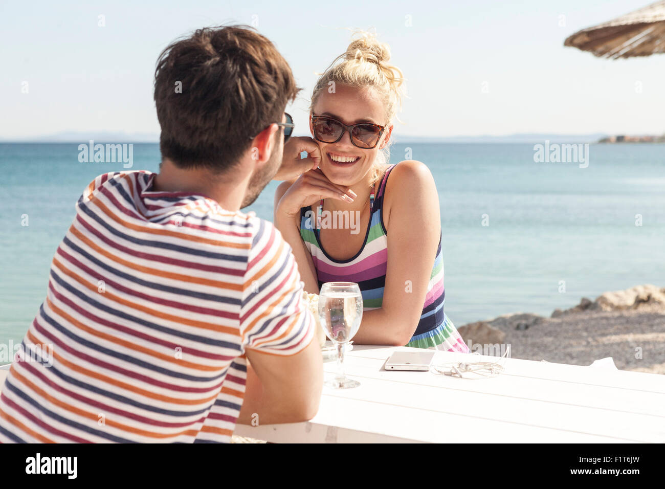 Young couple sitting at table in beach bar - Stock Image
