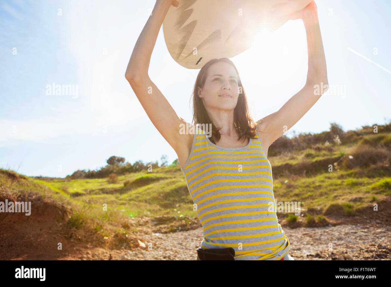 Woman carrying surfboard - Stock Image