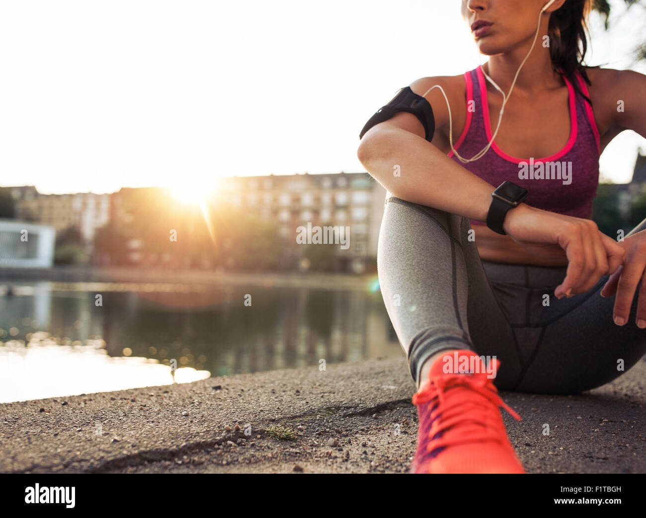 Young woman runner resting after workout session on sunny morning. Female fitness model sitting on street along - Stock Image