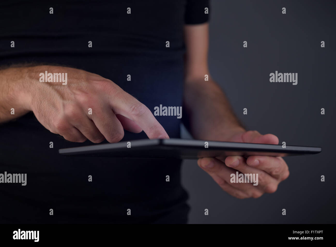 Digital tablet computer usage, man tapping touch screen of movable electronics technology gadget, close up of hands, - Stock Image
