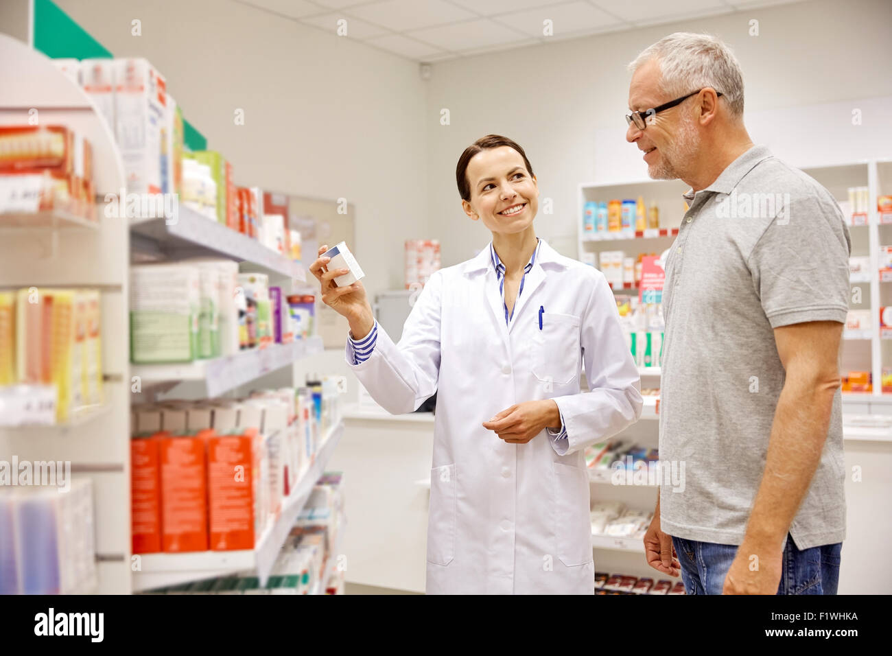 pharmacist showing drug to senior man at pharmacy - Stock Image
