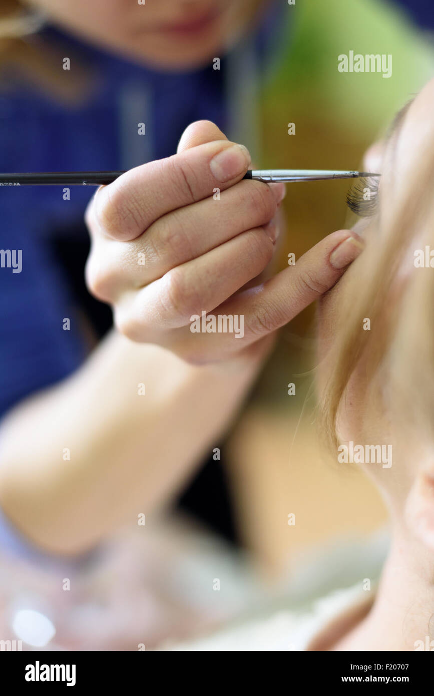 the makeup artist paint the eyes - Stock Image